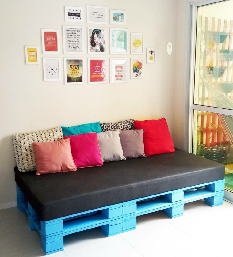 stanza arredata con delle panchine con bancali con seduta scura e cuscini colorati