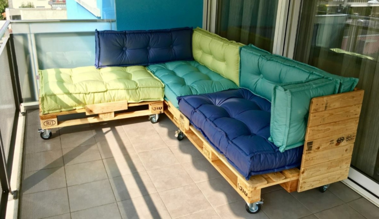 balcone arredato con dei divani in pallet completi di cuscini trapuntati verdi, blu e turchesi