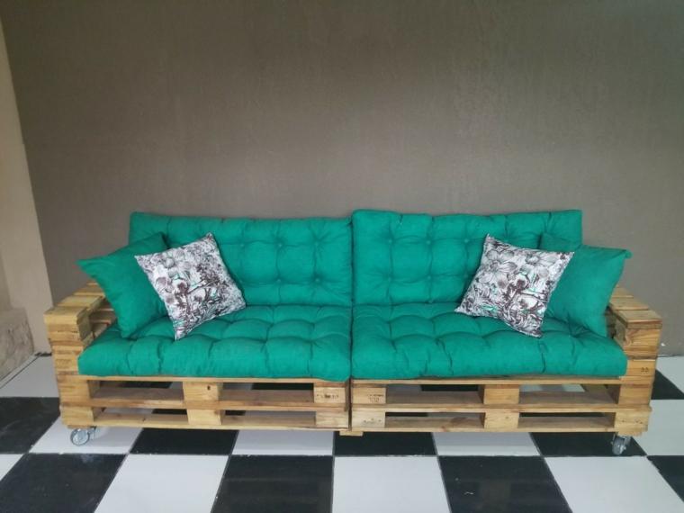 pavimento a scacchi bianco e nero e un divano pallet fai da te con cuscini trapuntati turchesi