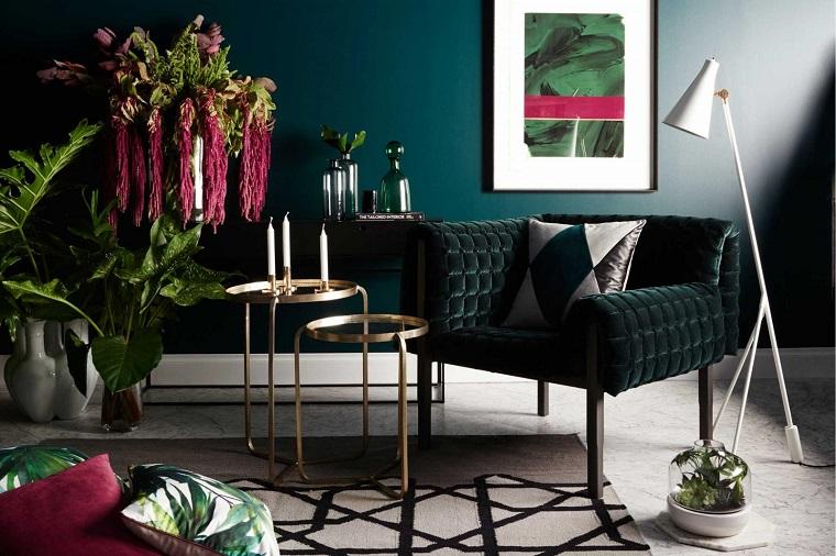 Case moderne interni, soggiorno con pareti di colore verde petrolio, decorazione con piante, arredare con poltrona e due tavolini rotondi