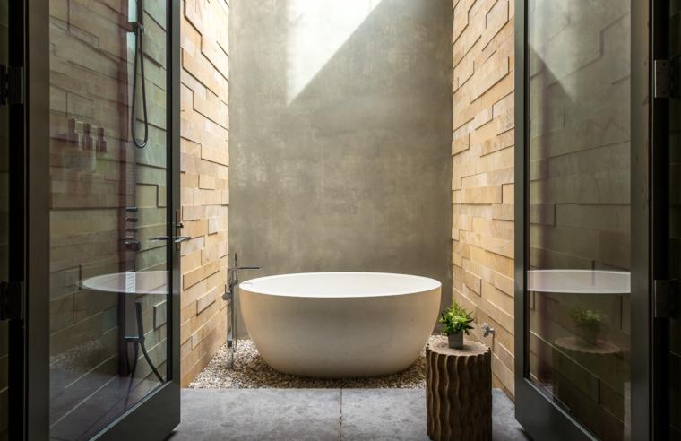 Piastrelle bagno moderni, parete con mattoni, pavimento rivestito sassi, vasca rotonda