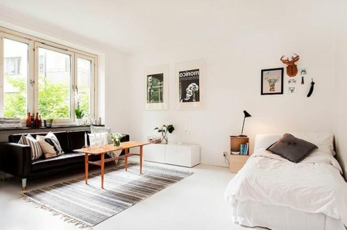 una proposta d'arredo per case piccolissime con un divano in pelle nera, tappeto e letto a una piazza e mezza