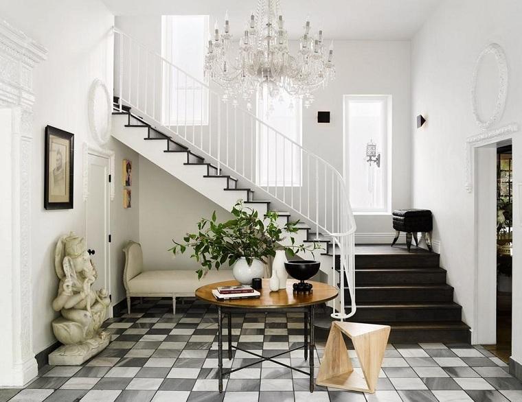 Interni casa, entrata di casa con pavimento in piastrelle bianco e nere, scale con ringhiera di ferro tinta di bianco