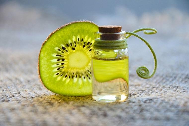 Pezzo di kiwi, olio essenziale agli agrumi, bottiglietta di vetro con tappo di sughero