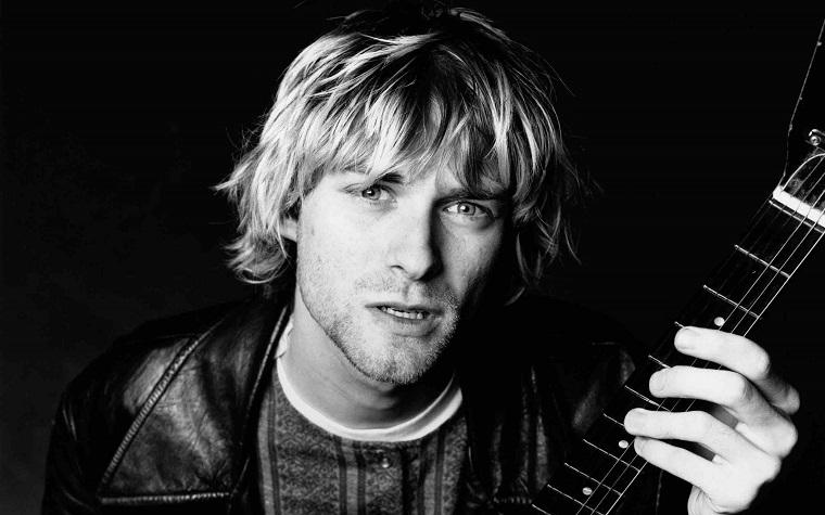 Il cantante Kurt Cobain con capelli lunghi di colore biondo, chitarra in mano