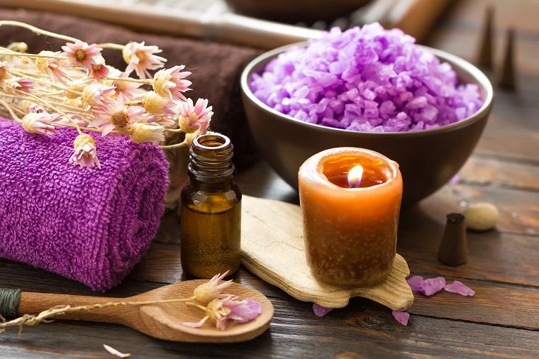 Piatto tondo di legno con sali viola, candela profumata, oli essenziali in bottiglietta di vetro