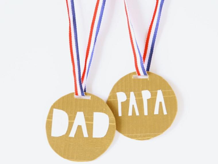 cartoncini con la scritta papà in bianco, delle medaglie come lavoretti festa del papà