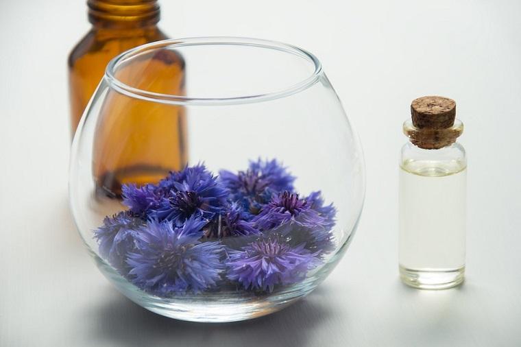 Bottiglia piccola di vetro con tappo di sughero, petali di fiore viola, aromaterapia e cura con essenze vegetali