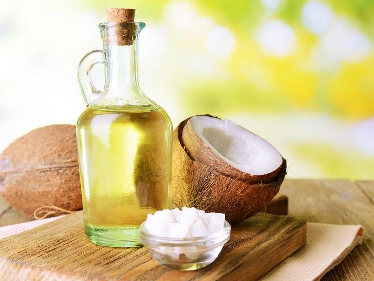 Oli essenziali bio, olio di cocco in bottiglia di vetro, tagliere di legno, tappo di sughero