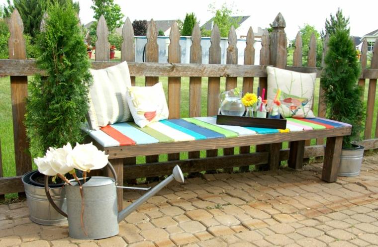 panchina realizzata riciclando dei bancali con dei cuscini, piante e innaffiatoio