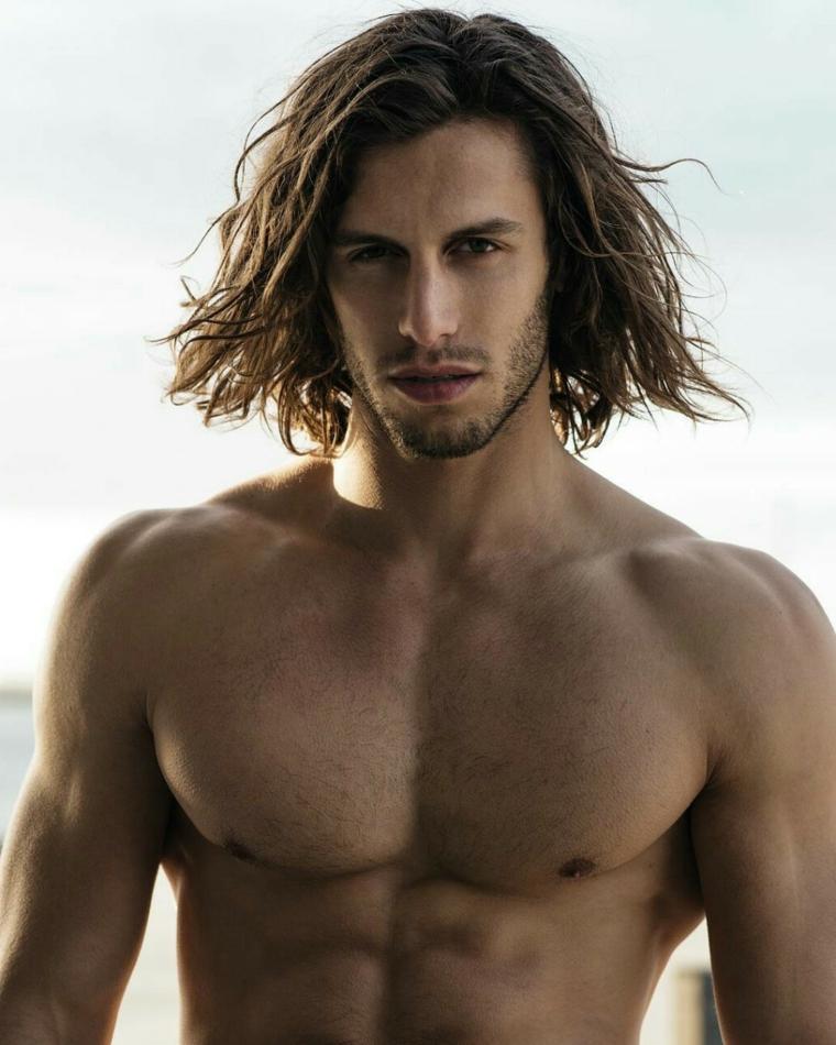 Ragazzo in spiaggia, tagli di capelli uomo lunghi, acconciatura mossa di colore castano