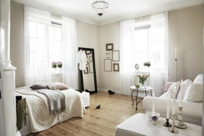 una soluzione per arredare monolocale con un divano bianco, pareti e tende bianche, parquet chiaro e specchio con cornice nera
