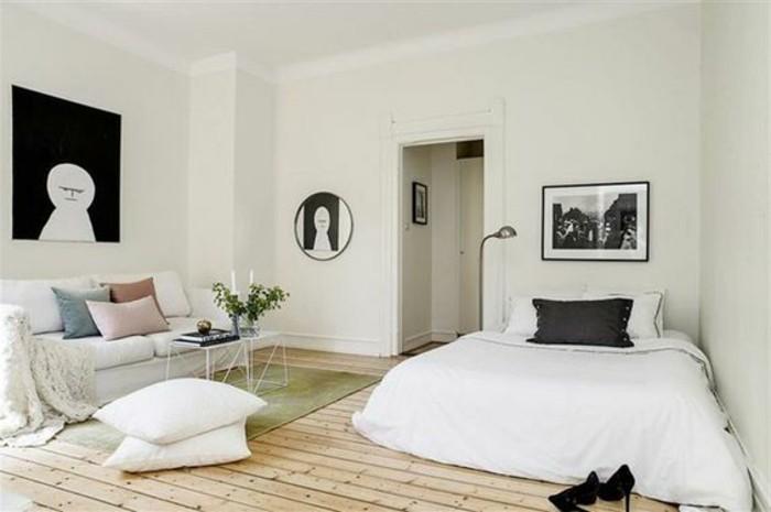 un'idea per arredare mini appartamento con un letto a due piazze, un divano bianco, pareti bianchi e parquet