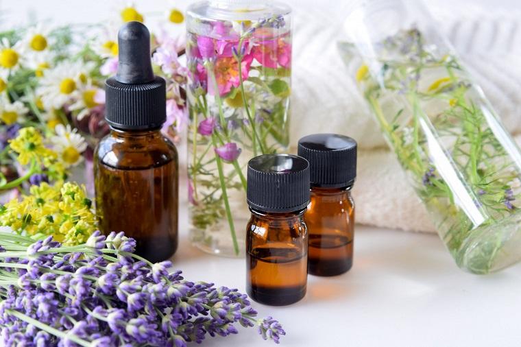 Olio eterico di diverse essenze, fiori di lavanda e camomilla, bottigliette di vetro colore scuro
