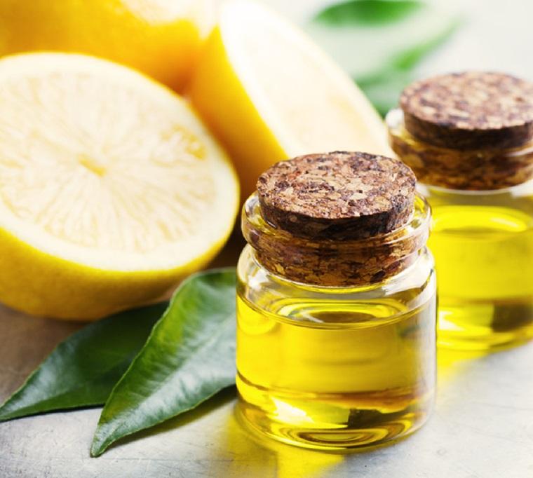 Barattolo di vetro con olio essenziale di limone, limoni tagliati a metà e foglie
