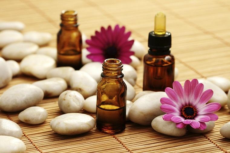 Aromaterapia con oli essenziali, bottigliette di vetro con essenze, decorazione con sassi e fiori