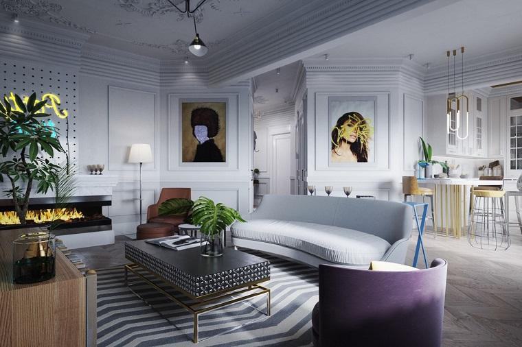 Soggiorno arredato con un divano di colore grigio chiaro e tavolino nero, cucina a vista con isola