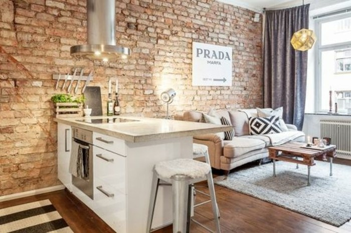 una penisola bianca con top beige, un divano beige, pareti con mattoni a vista: un'idea per arredare mini appartamenti