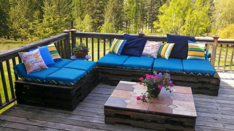 set d'arredo esterno realizzato con dei pallet completi di cuscini turchesi e tavolo quadrato