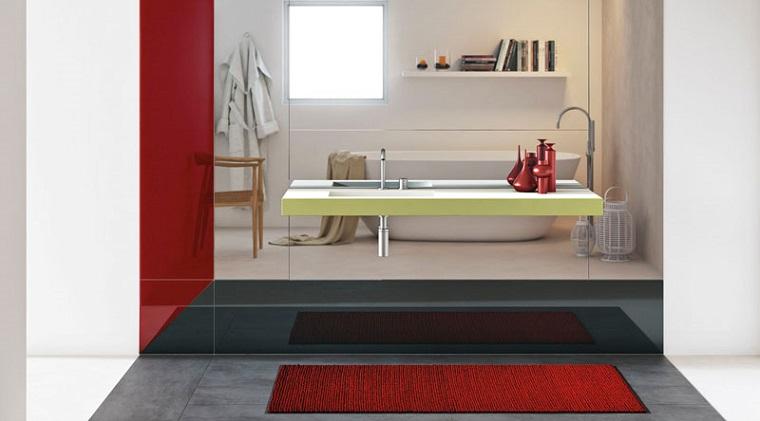 Come arredare un bagno, mobile colore giallo con lavandino, decorazioni in rosso, pavimento piastrelle nere con tappeto rosso