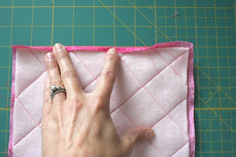 fase che mostra come viene piegato il bordo superiore della stoffa degli inviti per feste di compleanno fai da te