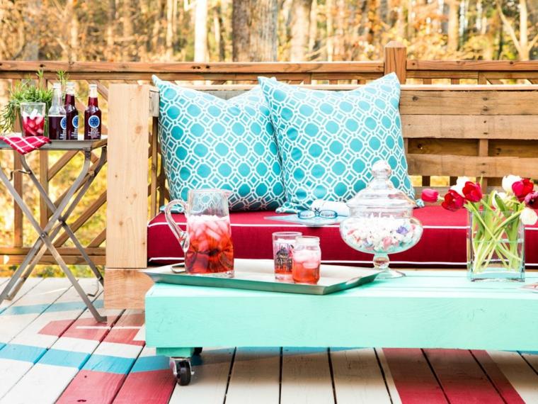 esterno arredato con un divano pallet con cuscini rossi e bianchi e turchesi e un tavolino con le rotelle