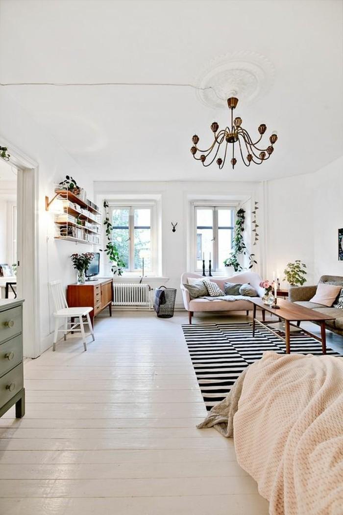 una soluzione per arredare un monolocale con un letto, due divani, una libreria sospesa e grandi finestre
