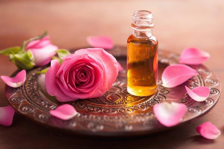 Oli essenziali per diffusori, petali di rosa e piattino di legno decorato, aromaterapia naturale