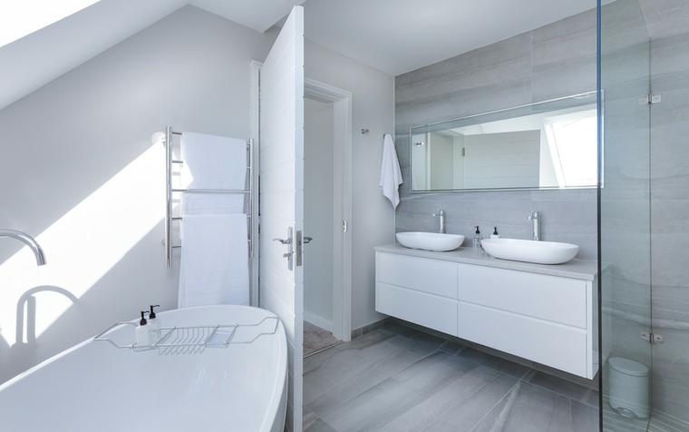 Rivestimenti bagni moderni immagini, vasca con accessorio di metallo, due lavandini su un mobile sospeso