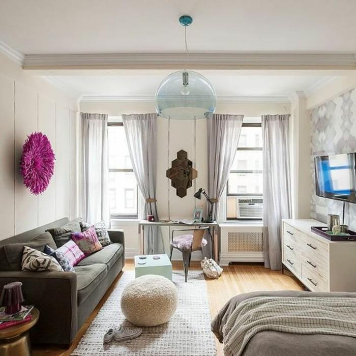 un'idea per arredare monolocale con divano grigio, due grandi finestre, sgabello tondo e mobile tv bianco