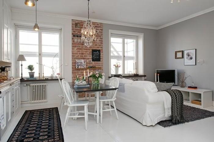 una proposta per come arredare un monolocale con pavimento, mobili della cucina e sedie bianche, tappetti scuri e parete con mattoni