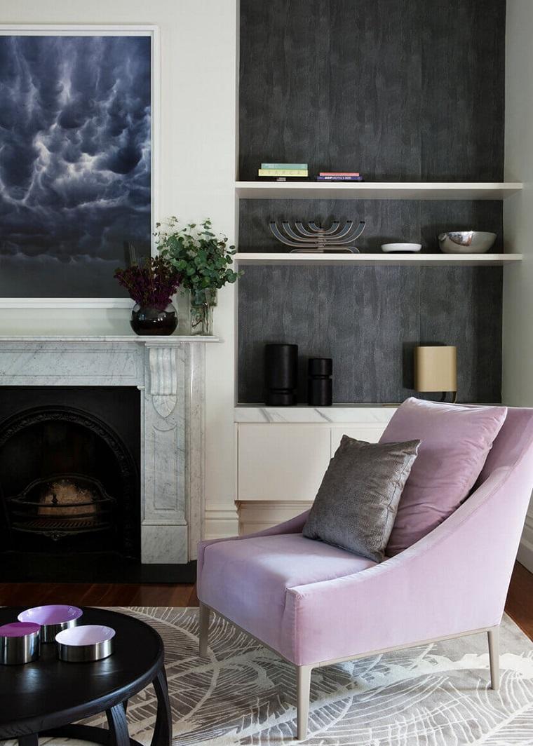Arredare con una poltrona di colore rosa, idee arredo casa, parete colore nero effetto sporco, camino con rivestimento di marmo