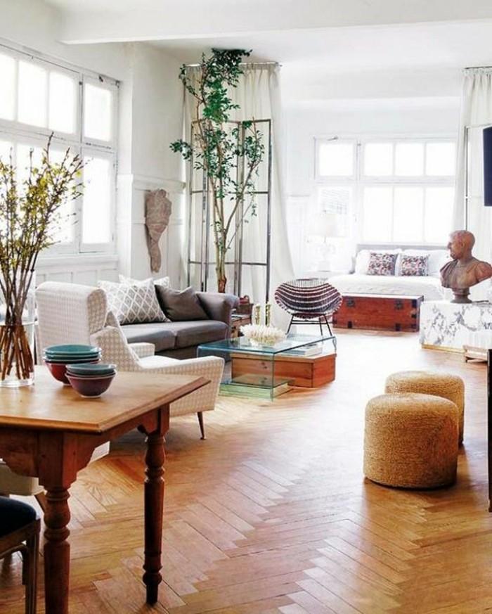 un pavimento in parquet, tavolo in legno, un divano grigio, piante e oggetti d'arte per arredare monolocale