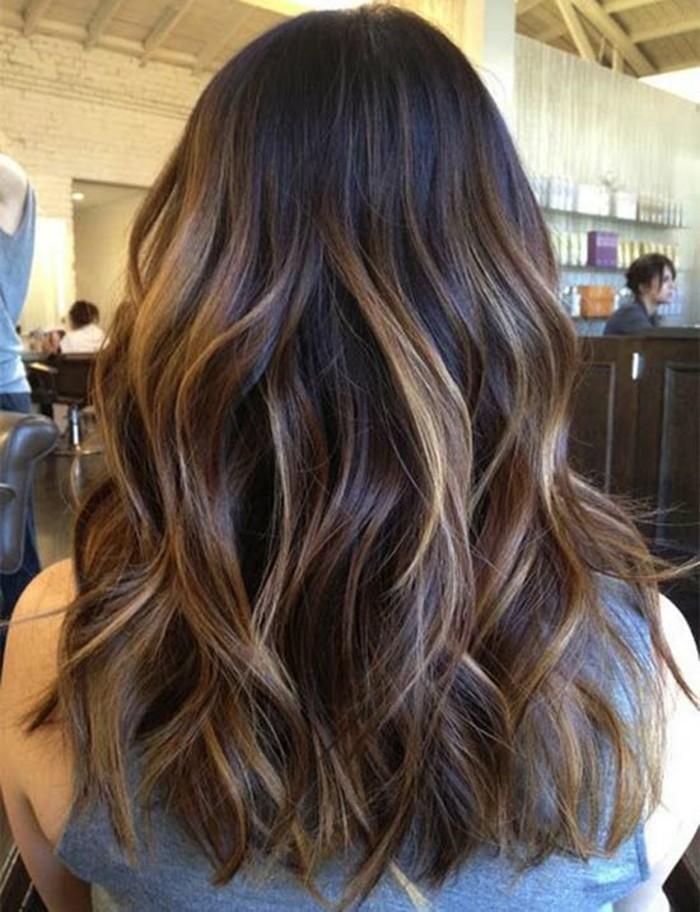 una ragazza con i capelli lunghi castano scuro con dei balayage color caramello