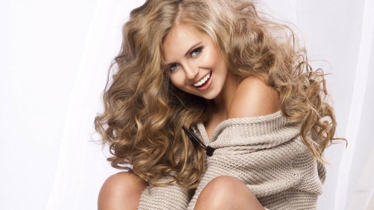 capelli ricci e lunghi colore nocciola con delle sfumature bionde, occhi azzurri e rossetto arancione chiaro