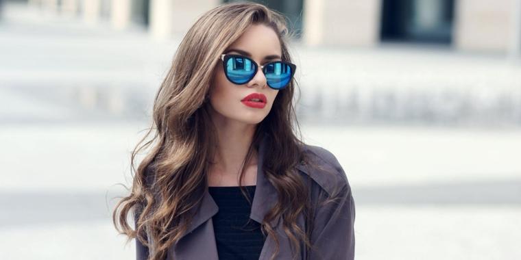 idea per dei capelli color nocciola lunghi e con delle morbide onde, rossetto rosso e occhiali a specchio