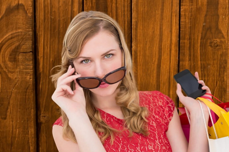 bellissima ragazza con gli occhi verdi e i capelli biondo ramati, occhiali da sole e rossetto arancio