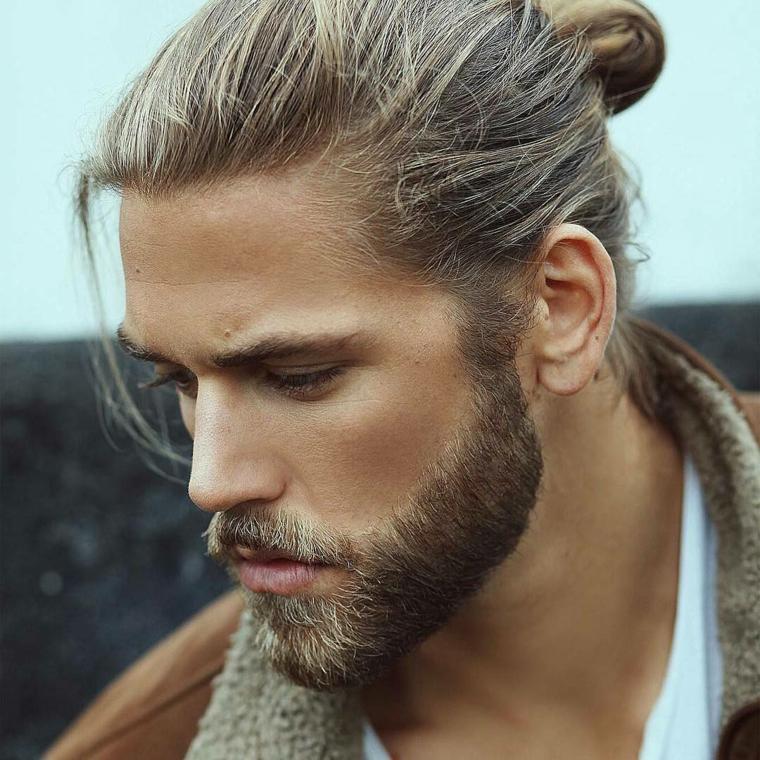 Uomini belli, ragazzo con capelli biondi, lunghi e legati a chignon, barba di media lunghezza