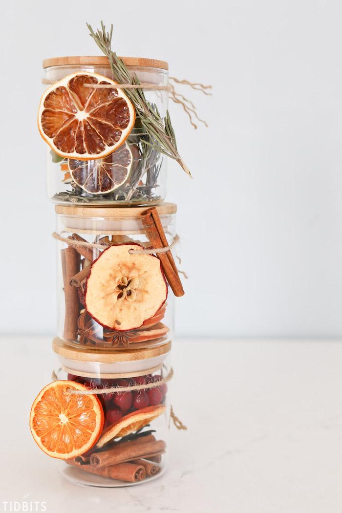 Barattoli di vetro con frutta secca, pensierini di Natale fai da te, bastoncini di cannella e rosmarino essiccato
