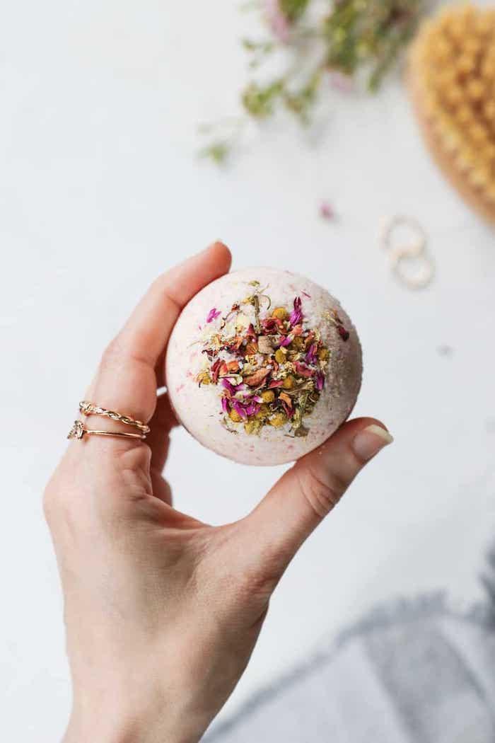 Idea regalo per la mamma, sapone forma pallina con fiori secchi, donna che tiene una pallina