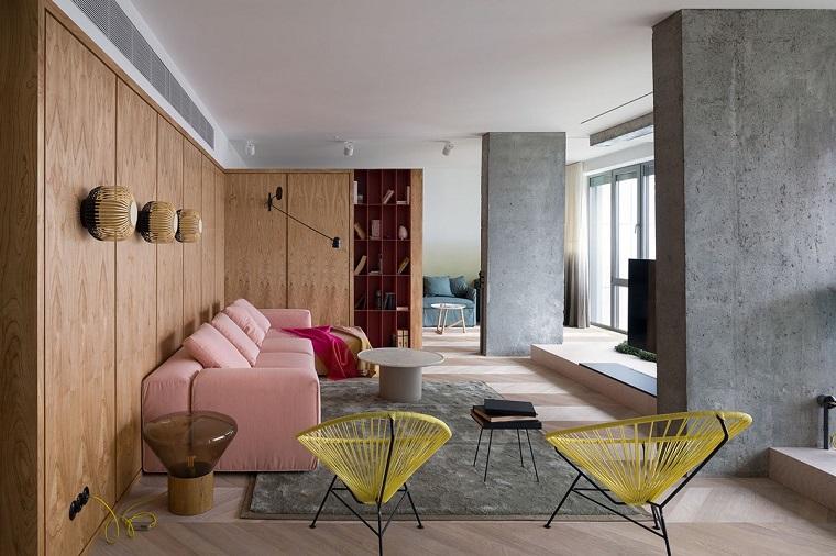 Soggiorno con un divano di colore rosa, idee per arreda casa, pareti di legno con mensole