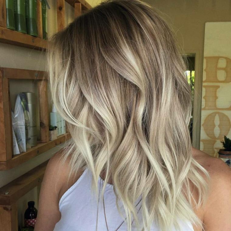 capelli di media lunghezza con un'acconciatura a onde e delle sfumature biondo dorato