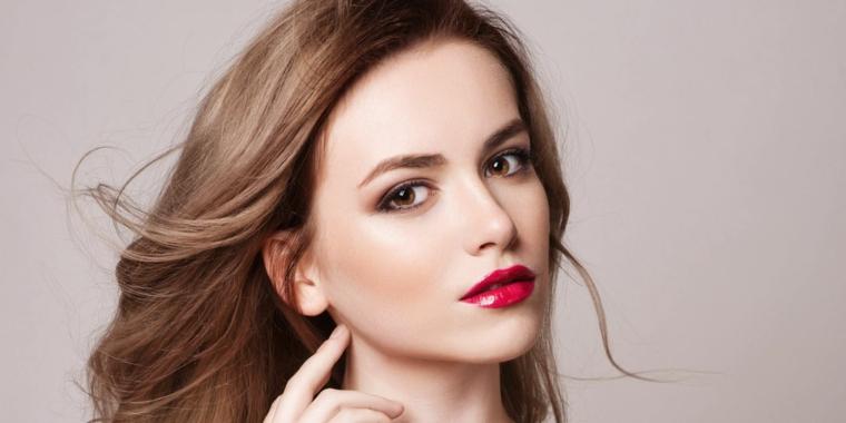 una ragazza con gli occhi marroni e i capelli color cioccolato e miele, rossetto rosso lucido