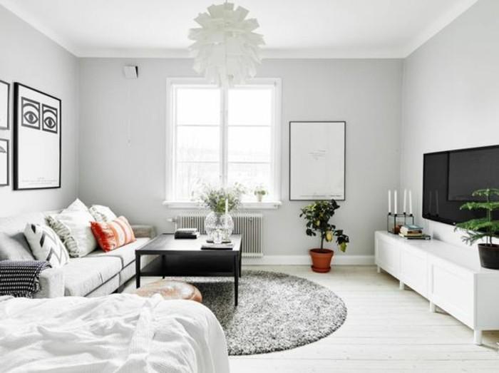 una zona living con un divano lineare, un tavolino quadrato nero, un mobile tv bianco e un tappeto rotondo