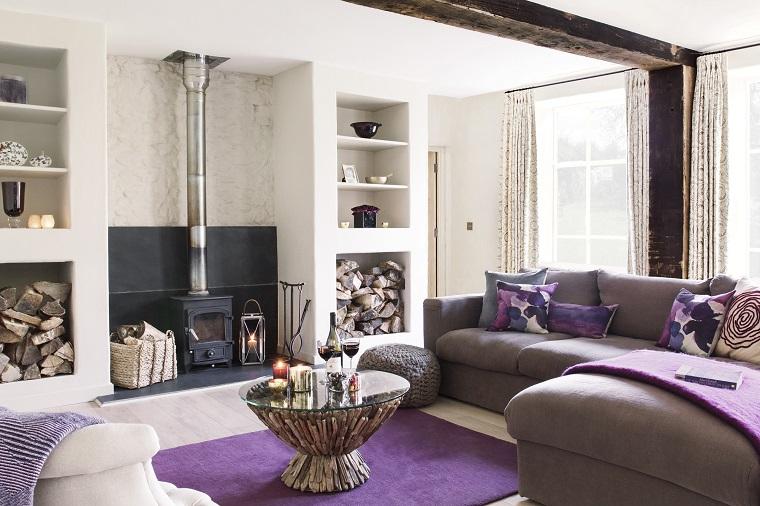 Soggiorno arredato con divano, tavolino con superficie in vetro forma rotonda, stufa a legna
