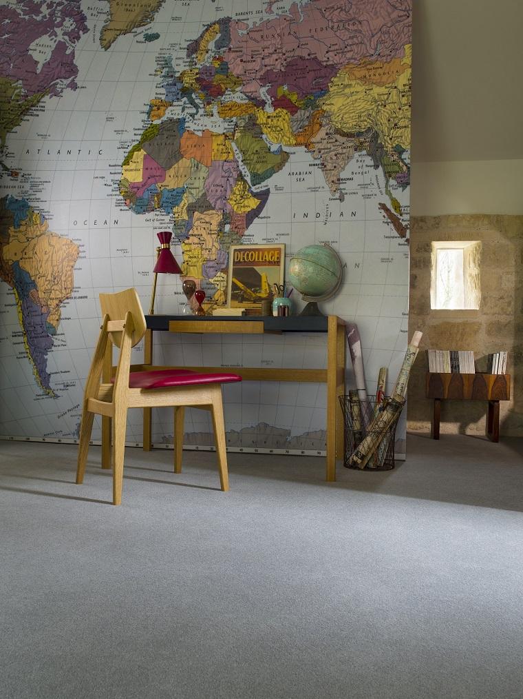 Ufficio in casa arredato con scrivania e sedia con seduta colore rosso in pelle, parete con carta da parati disegno mappamondo, interni casa