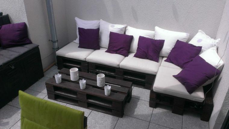 stanza con dei divani con bancali completi di cuscini bianchi e viola e un tavolino da caffè