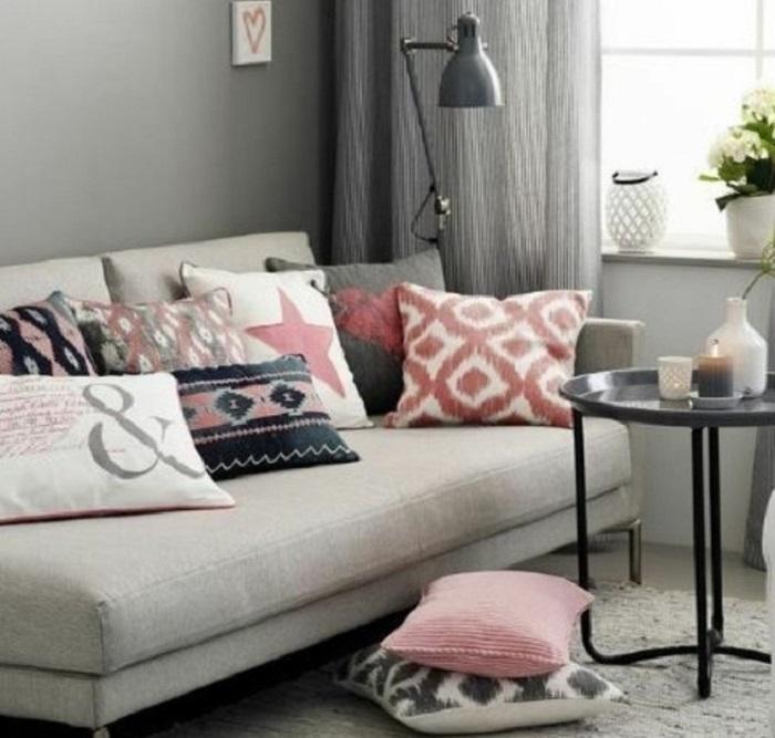 Colori da abbinare al grigio, divano con tanti cuscini, tavolino basso rotondo e tappeto