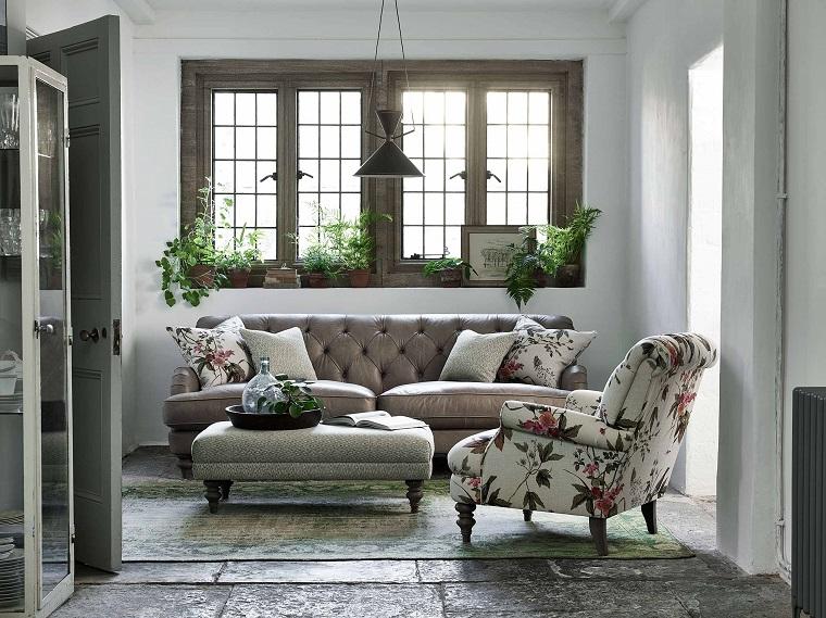 Case moderne interni, salotto con mobili, divano in pelle colore beige, poltrona in tessuto motivi floreali, pavimento pietra con tappeto