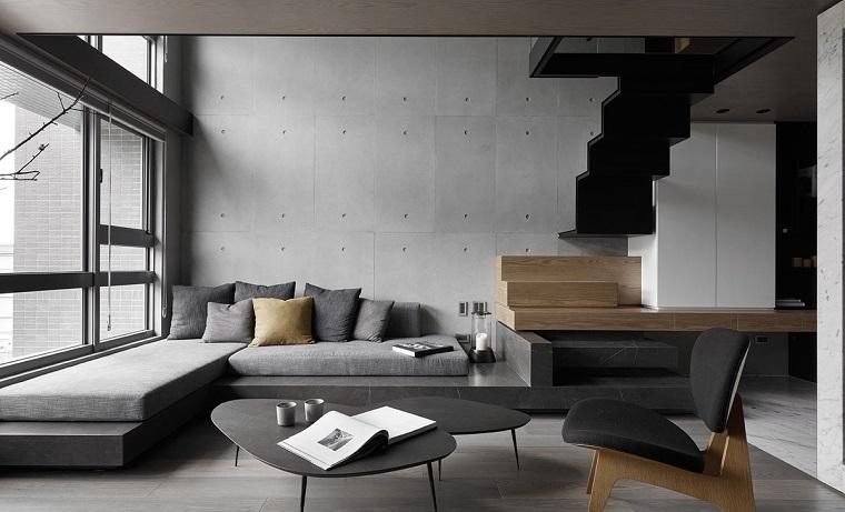 Stili di arredamento, soggiorno con un divano di colore grigio ad angolo e tavolino basso di design